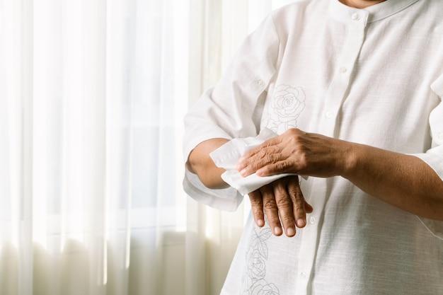 Donna maggiore che pulisce le sue mani con carta velina morbida bianca. isolato su un sfondi bianchi