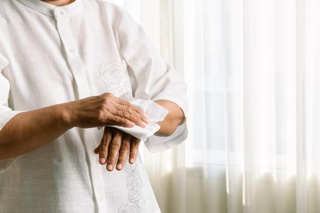 Donna maggiore che pulisce le sue mani con carta velina morbida bianca. isolato su un tavoli bianchi