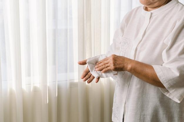 Donna maggiore che pulisce le sue mani con carta velina morbida bianca