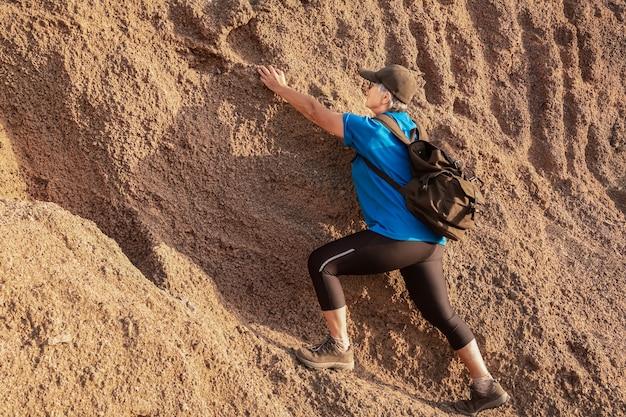 Donna maggiore che scala un'arida montagna vulcanica. un popolo caucasico che si gode la libertà e l'avventura