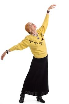 Senior donna che balla signora isolata con le braccia tese volo dell'anima