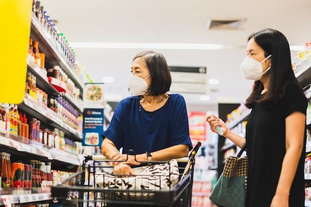Donna anziana e figlia in maschera medica che fanno shopping al supermercato