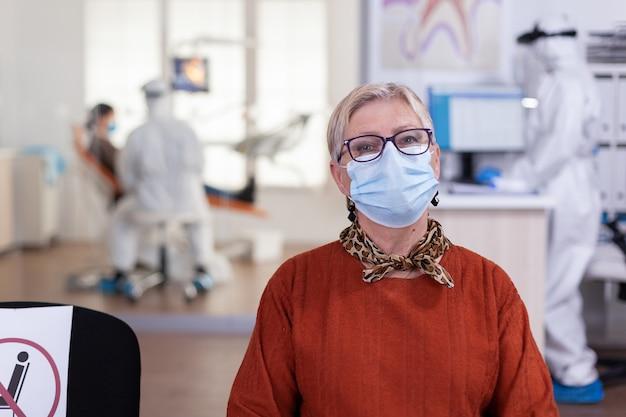Donna anziana in clinica odontoiatrica che indossa una maschera facciale che guarda la telecamera in attesa di consultazione durante la pandemia globale con coronavirus