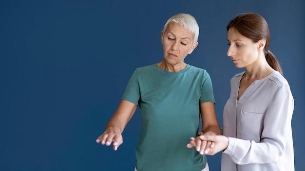 Donna anziana che fa una sessione di terapia occupazionale con uno psicologo con spazio per le copie