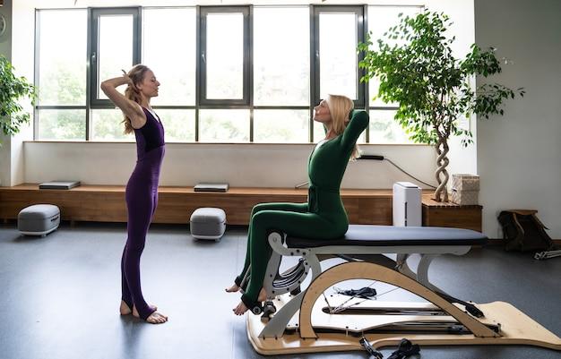 Senior donna facendo riabilitazione fisica e pilates con il suo allenatore nel centro sportivo