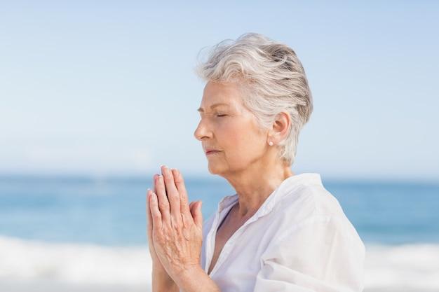 Donna maggiore che fa yoga