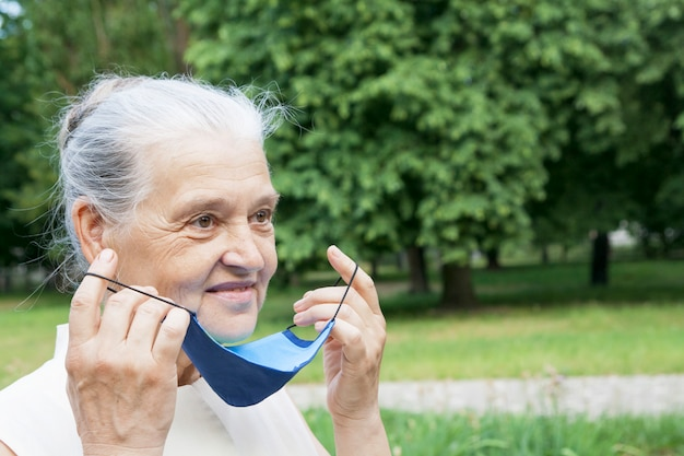 La donna senior veste o toglie la maschera protettiva all'aperto.