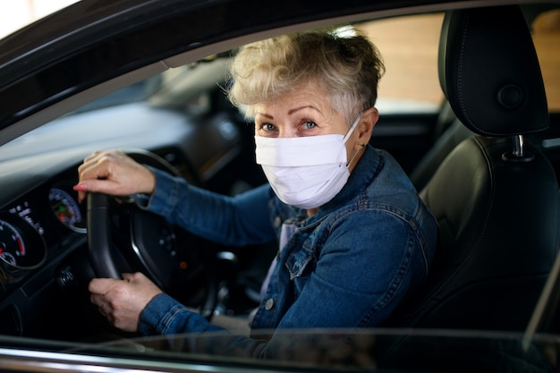 Autista donna anziana con maschera facciale in auto, virus corona e concetto di quarantena.