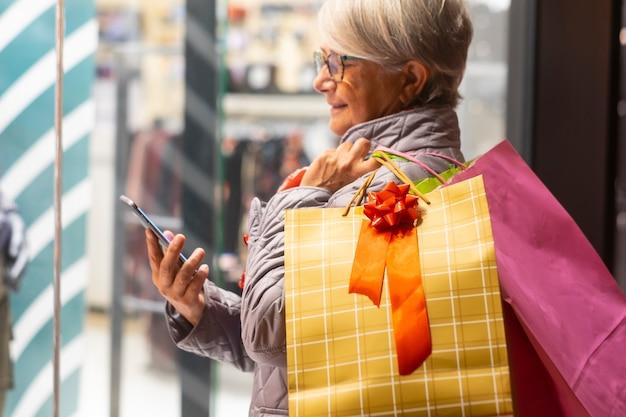 Donna anziana che si gode lo shopping serale guardando il suo smartphone. concetto di consumismo e anziani tecnologici e sociali