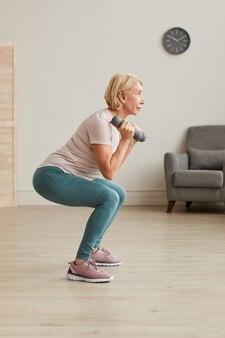 Senior donna che si esercita con manubri durante l'allenamento sportivo a casa