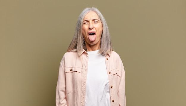 Donna anziana che si sente disgustata e irritata, sporge la lingua, non ama qualcosa di brutto e schifoso