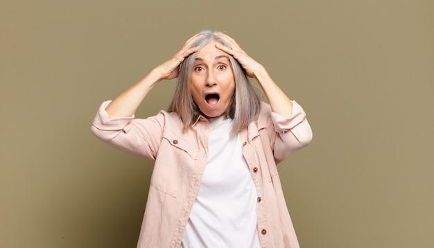 Donna anziana che si sente inorridita e scioccata, alza le mani alla testa e si fa prendere dal panico per un errore