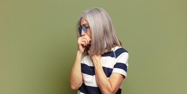 Senior donna che si sente male con mal di gola e sintomi influenzali, tosse con la bocca coperta