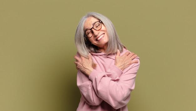 Donna anziana che si sente innamorata, sorride, si coccola e si abbraccia, rimane single, è egoista ed egocentrica