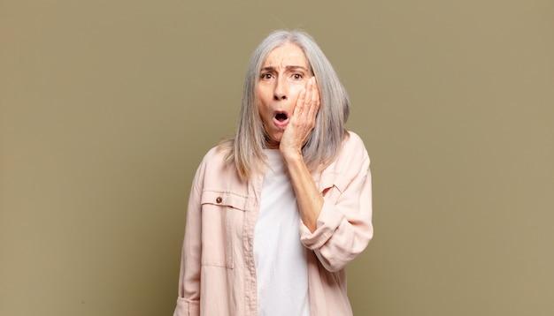 Senior donna sentirsi scioccata e stupita tenendo faccia a mano incredula con la bocca spalancata