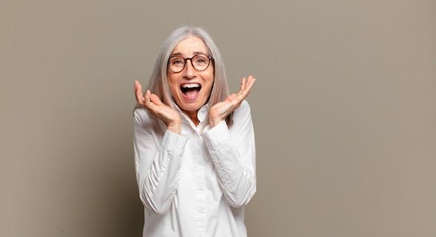 Senior donna che si sente scioccata ed eccitata, ridendo, stupita e felice a causa di una sorpresa inaspettata