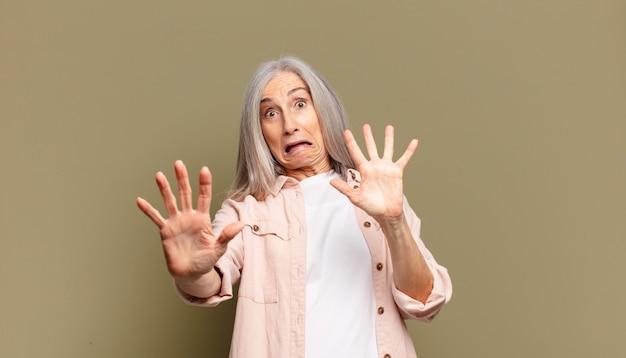 Donna anziana che si sente terrorizzata, indietreggia e urla di orrore e panico