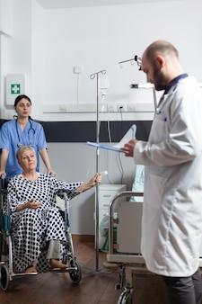 Senior donna ottenere la medicina attraverso la linea endovenosa borsa seduta su carrozzina spinto dall'infermiera nella stanza di ospedale