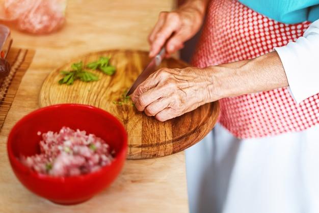Mani senior della donna che tagliano le verdure su una tavola di legno in cucina