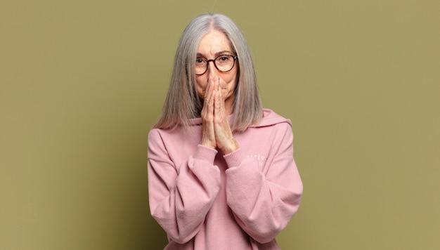 Senior donna felice ed emozionata, sorpresa e stupita che copre la bocca con le mani, ridendo con un'espressione carina
