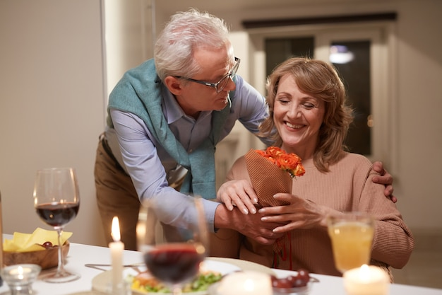 Senior donna felice con i fiori mentre cenano con il marito a casa