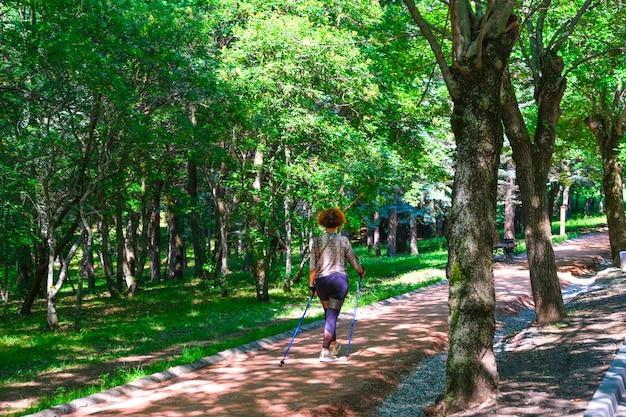 La donna maggiore ha la felicità da esercizio nel parco, mantenendo la salute della donna anziana nel concetto di pensionamento