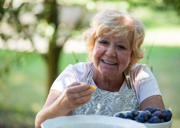 Donna senior che mangia albicocca in giardino