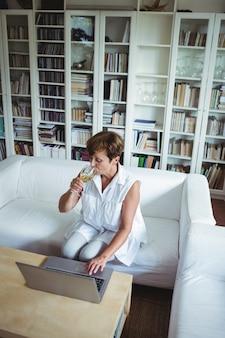 Donna senior che mangia un bicchiere di vino mentre per mezzo del computer portatile