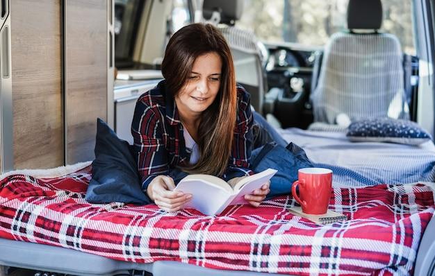Donna anziana che ha dentro il camper mentre legge un libro e beve caffè - focus sul viso