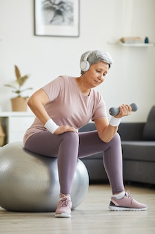Senior donna in cuffia ascoltando musica ed esercitando con manubri sulla palla fitness nel soggiorno di casa