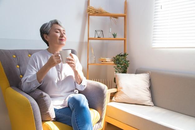 Senior donna in possesso di una tazza di caffè o tè rilassante a casa al mattino.