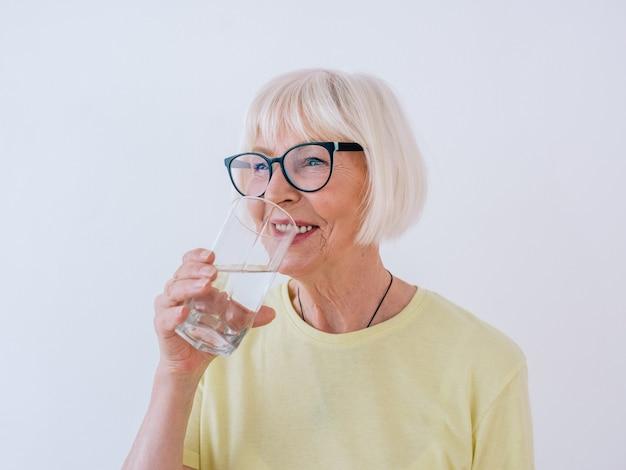 Donna anziana che tiene in mano un bicchiere d'acqua e acqua potabile stile di vita sano sport concetto anti età