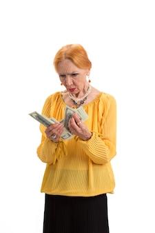 Senior donna in possesso di denaro isolato signora seria guardando contanti scegliere il miglior fondo pensione