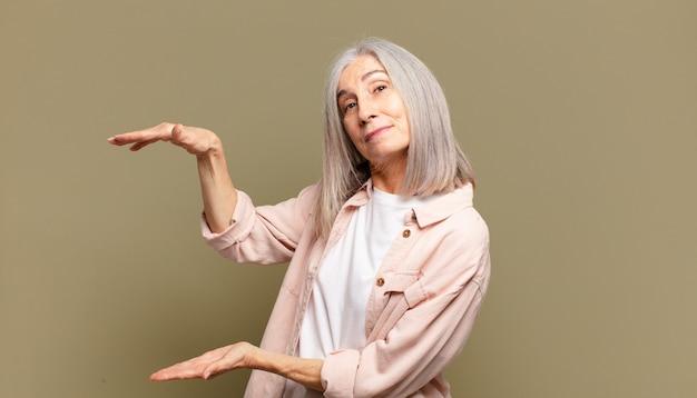 Donna anziana che tiene un oggetto con entrambe le mani sullo spazio della copia laterale, mostra, offre o pubblicizza un oggetto