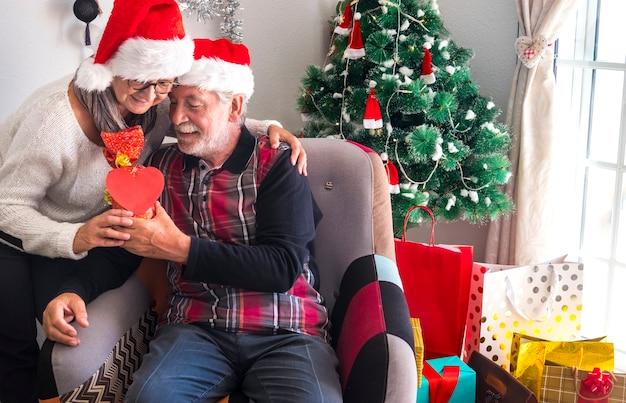 Senior donna che abbraccia il marito dandogli un regalo di natale. entrambi indossano cappelli di babbo natale: buon natale e un'espressione d'amore per due anziani in pensione che si godono le vacanze