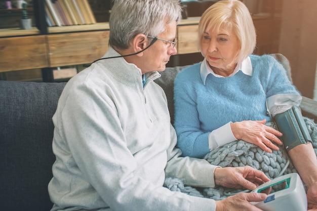 La donna maggiore sta misurando la sua pressione sanguigna con un dispositivo speciale