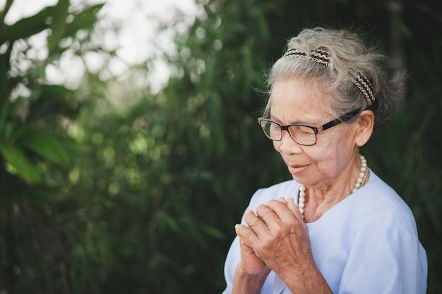 La donna anziana sta pregando con gli occhi chiusi sullo sfondo verde della natura