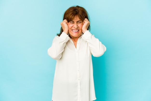 Senior donna isolata che copre le orecchie con le mani