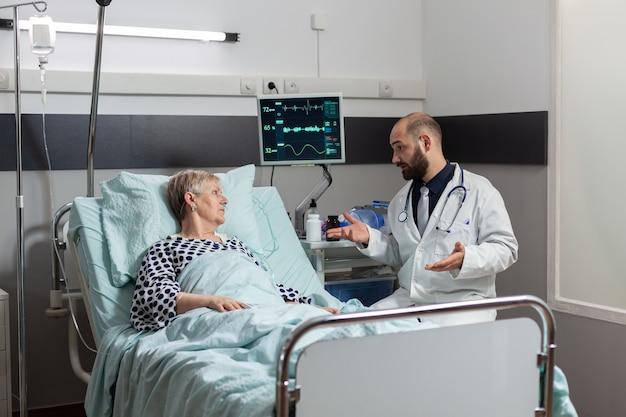 Senior donna sdraiata a letto inspira ed espira con l'aiuto del tubo dell'ossigeno, ricevendo un trattamento endovenoso da flebo iv
