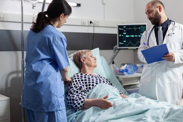 Senior donna sdraiata nel letto di ospedale che riceve farmaci attraverso una linea endovenosa