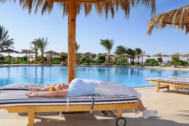 La donna anziana si trova sulla chaise longue, vicino alla piscina d'acqua nell'hotel resort-spa