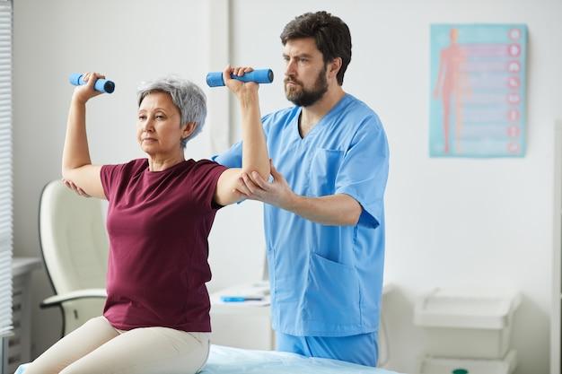 Senior donna sollevamento manubri e medico maschio che la assiste durante la riabilitazione