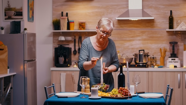 Senior donna accendere la candela in attesa di suo marito per una cena romantica. anziana vecchia moglie che prepara un pasto festivo con cibo salutare per la celebrazione dell'anniversario, seduta vicino al tavolo in cucina.