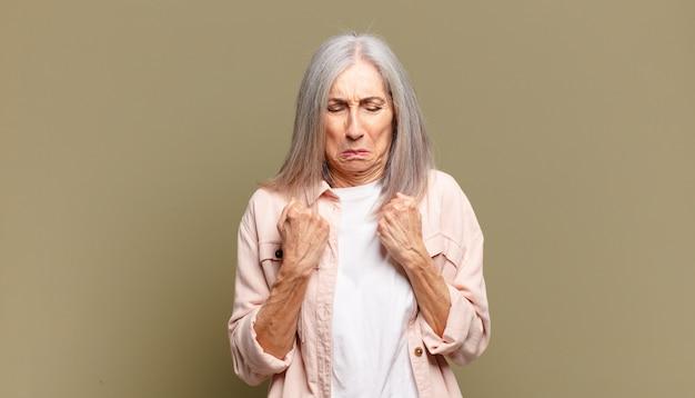 Senior donna che sembra fiduciosa, arrabbiata, forte e aggressiva, con i pugni pronti a combattere in posizione di boxe