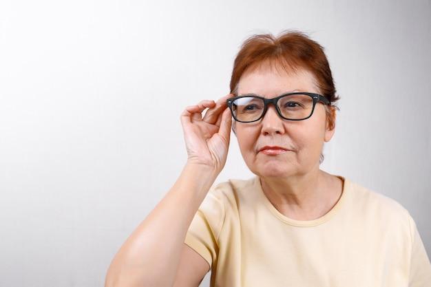 La donna senior distoglie lo sguardo con i vetri su bianco in una maglietta leggera.