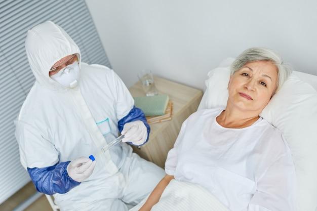 Donna senior sdraiata sul letto in reparto ospedaliero con il medico che indossa l'uniforme protettiva seduta accanto a lei