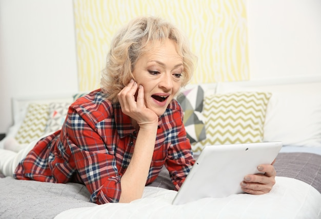 Donna anziana che effettua una videochiamata dal tablet a casa