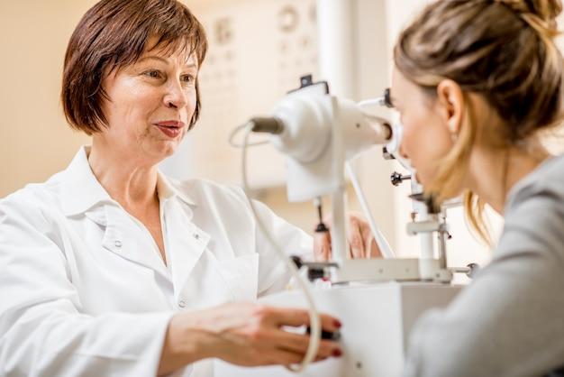 Oftalmologo donna anziana che controlla la vista con un dispositivo laser per la giovane paziente seduta in ufficio