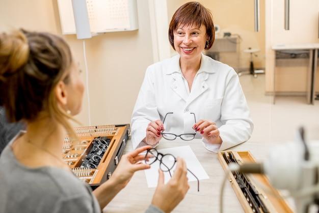 Oftalmologo senior della donna con il giovane paziente femminile durante la consultazione nell'ufficio oftalmologico