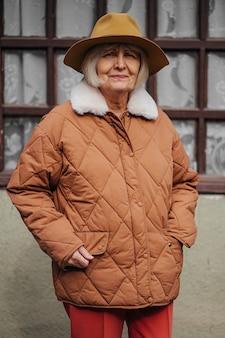 Senior donna fuori casa di campagna. donna anziana in capispalla alla moda